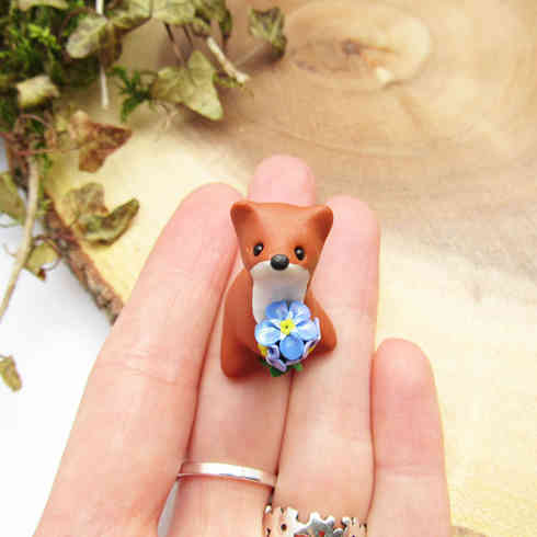 Weasel figurine with forget-me-not flowers
