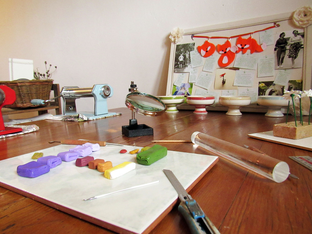 My work table with polymer clay, tools and inspiration board