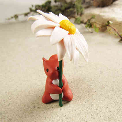 Tiny red squirrel with daisy
