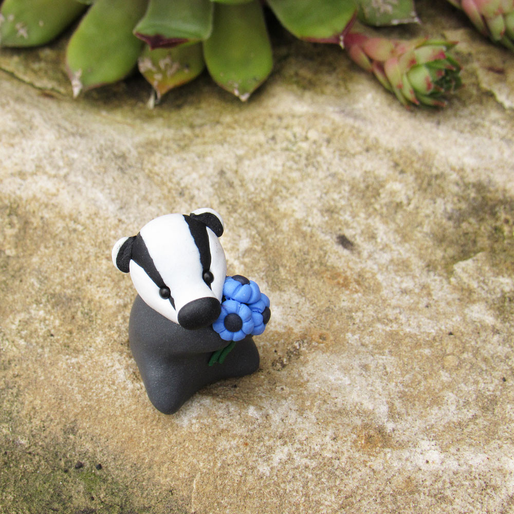 Tiny badger ornament with blue flowers