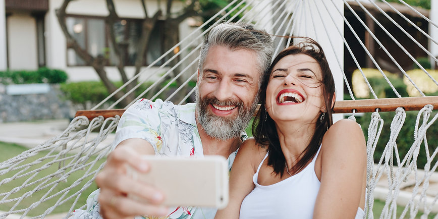 Couple sitting in hammock laughing