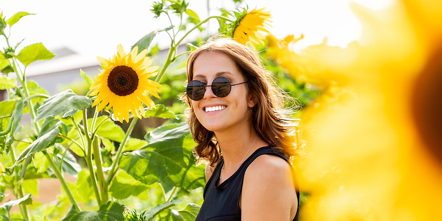 Woman wearing sunglasses laughing in sunflower field