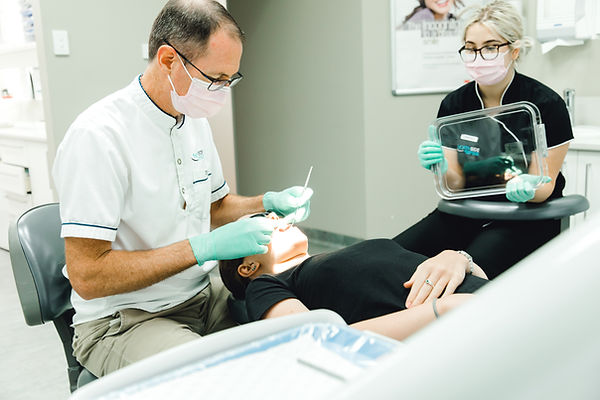 Northside Orthodontist Dr Tom Oliver performing treatment on patient in dental chair