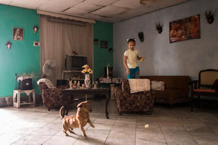 Inside a home in Havana, a young girl feeds some bread to her dog