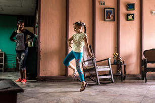 Inside a home in Havana, a young girl dances for her Mom