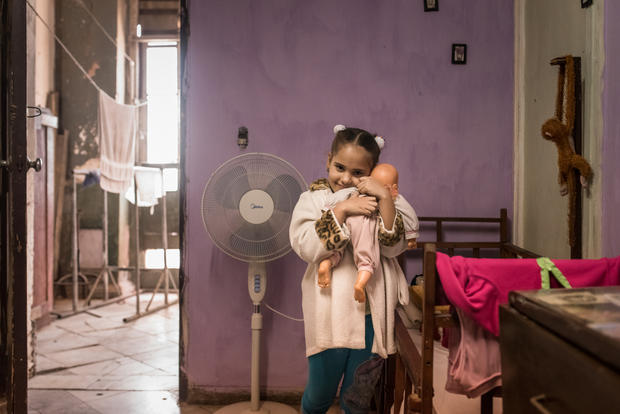 Inside a home in Havana, a young girl poses with her beloved doll
