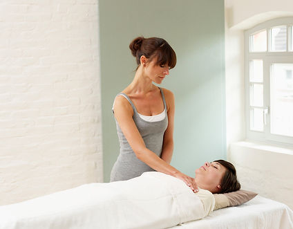 woman-receiving-reiki-treatment-from-mas