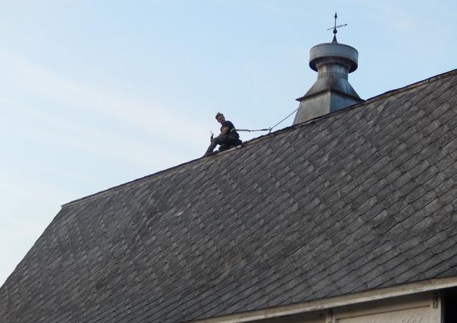Fixing a few loose shingles on barn roof