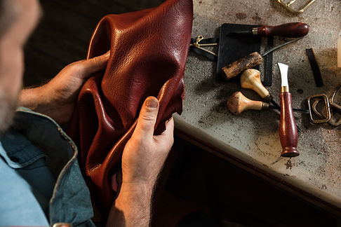 Craftsman touching leather, close-up. A