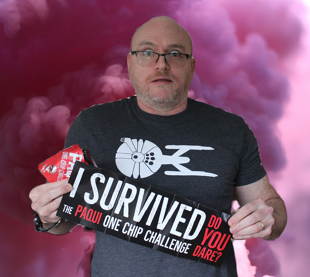 """Jeremy holding a sign that says """"I survived"""" in front of smoke"""