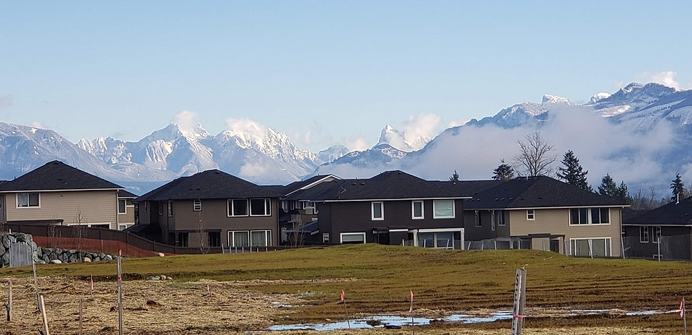 An image of snow-capped peaks behind homes