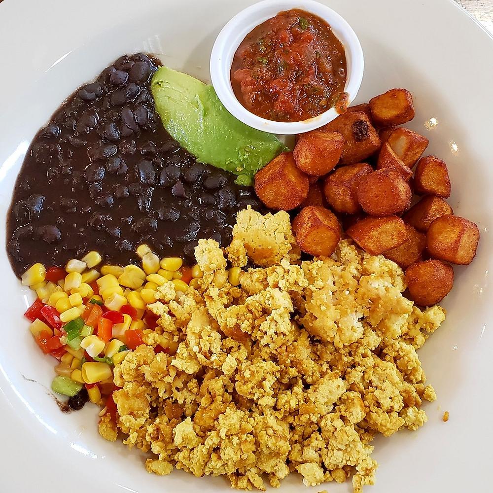 A plate with tofu scramble, home fries, black beans, avocado and salsa