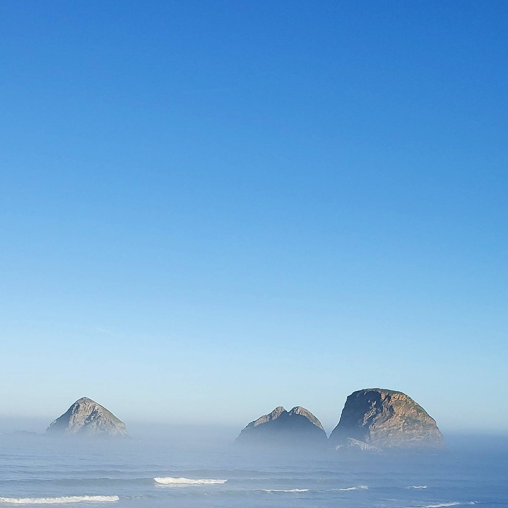 Rock formations rising from mist over the ocean