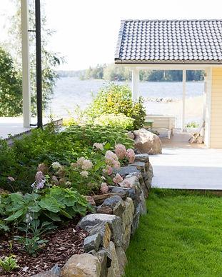 Puutarhassa on luonnonkivistä rakennettu kukkapenkki, jossa kasvaa peennoja. Edessä on hoidettu nurmikko, tausalla mökki ja järvimaisema.