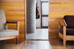 Entrance hall through sliding doors with curved buff brick wall.
