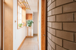 Corridor leading to two bedrooms with shower room , plant room and workshop beyond