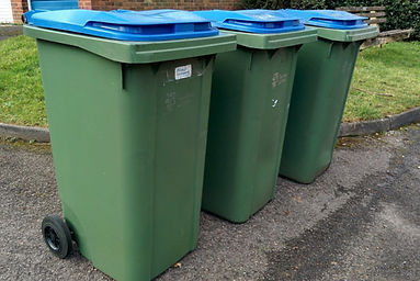 Three green recycling bins with blue lids