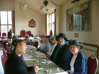 Ladies in hats at Clapham and Patching WI 80th birthday in village hall