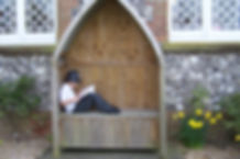 Child reading on seat outside school