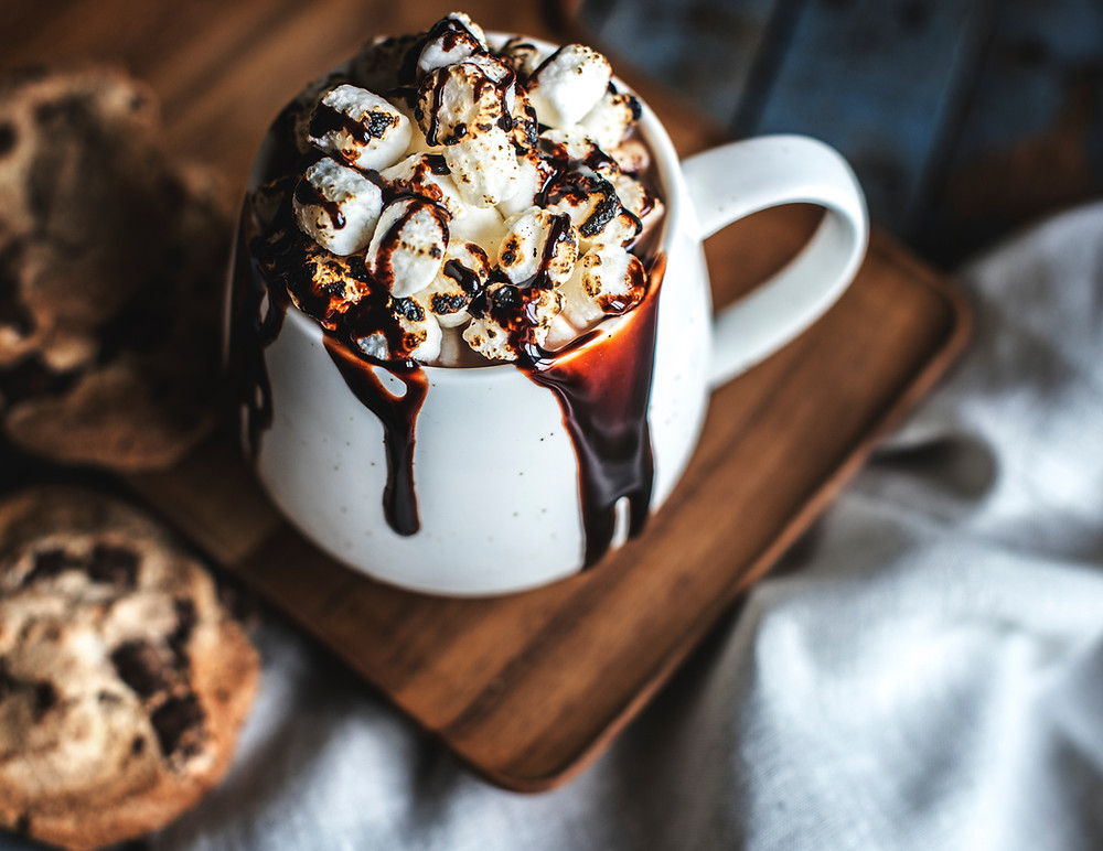 hot cocoa in mug with marshmallows on top and chocolate syrup drizzling over with chocolate chip cookie to side