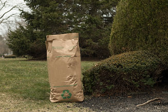 A brown lawn bag is full, next to a trim