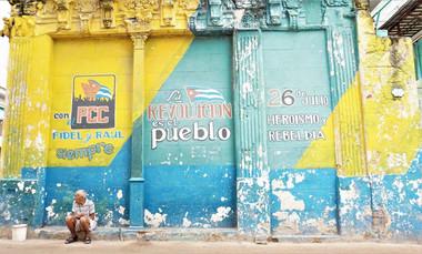 Cuban man by street advertising artwork, Havana, Cuba