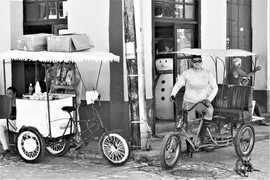 Vendors and cycle rickshaw in the streets of Trinidad, Cuba