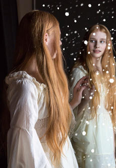 image of redhead girl looking in mirror