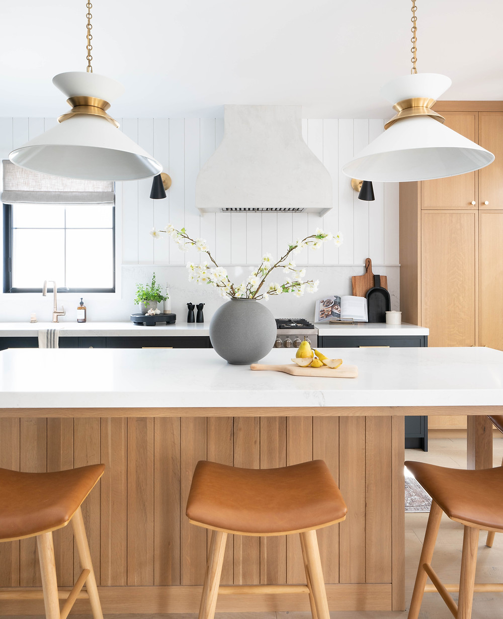 The custom range hood brings a soft yet substantial touch to the kitchen's back wall. Once an almost bare space, this wall now houses the plaster finished piece which is flanked by modern sconces for additional task lighting and ambiance.