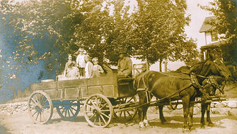 Children ride in a wagon as a delivery is made to the Silvis House in Rock Island, Illinois. This is one of Bethany's oldest photos.