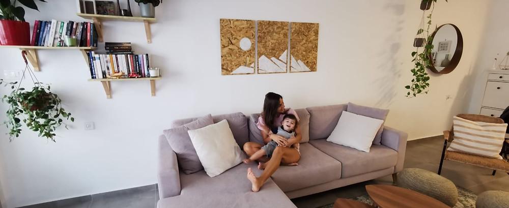 מחפשים אקססוריז לקיר הסלון? בתמונה ניתן למצוא את אחת הלקוחות המרוצות שלנו עם סט תמונות דקורטיביות מעץ ממוחזר מאחוריה
