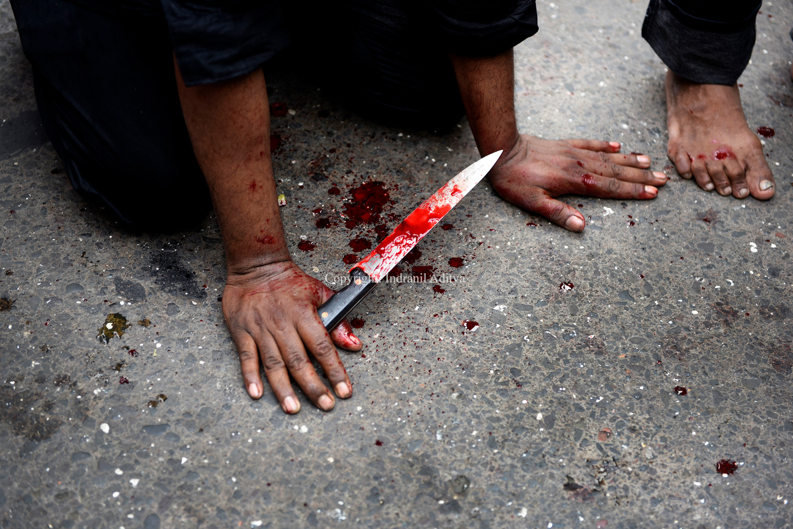 A man holds a knife during a procession of Muharram