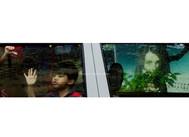 A boy looks through a window glass
