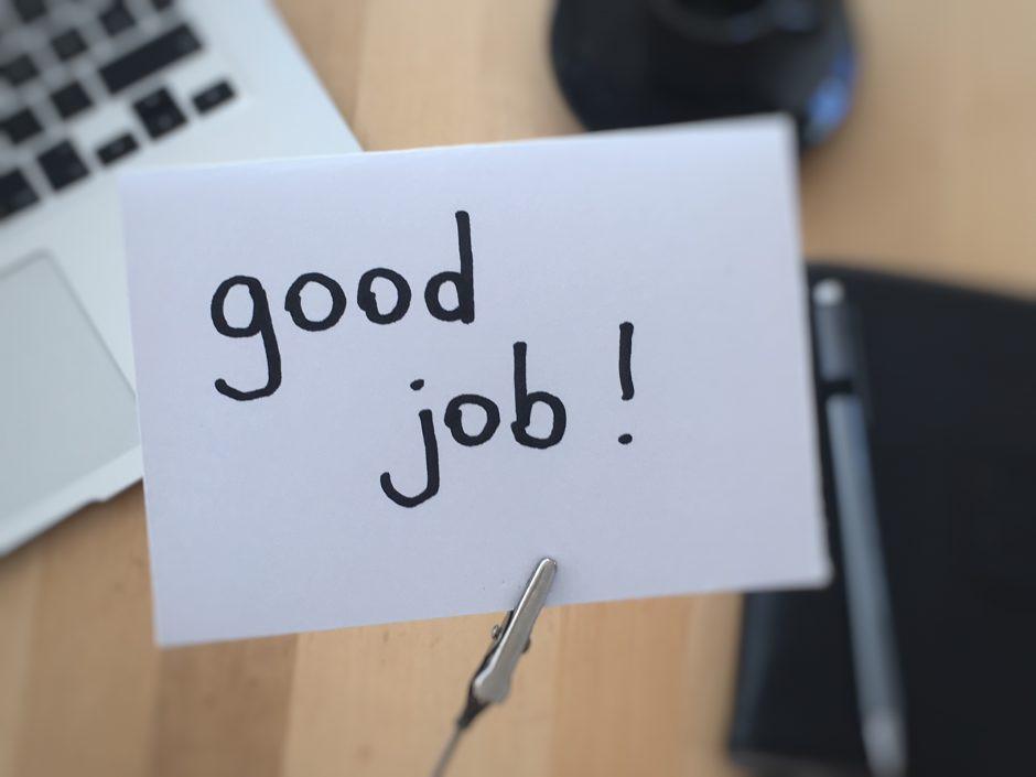 """Zettel mit """"good job!"""" vor Schreibtisch"""