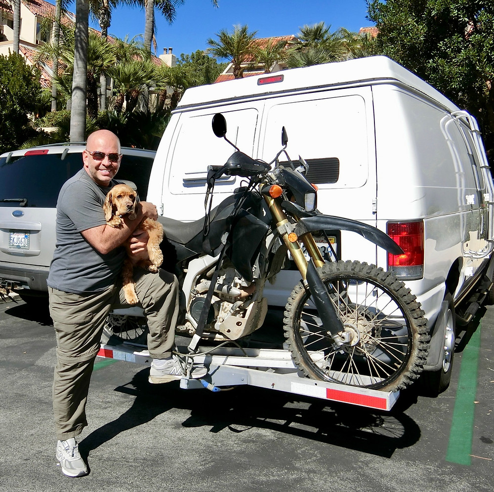 Gus posing with his puppy Hunny and his Van and Bike