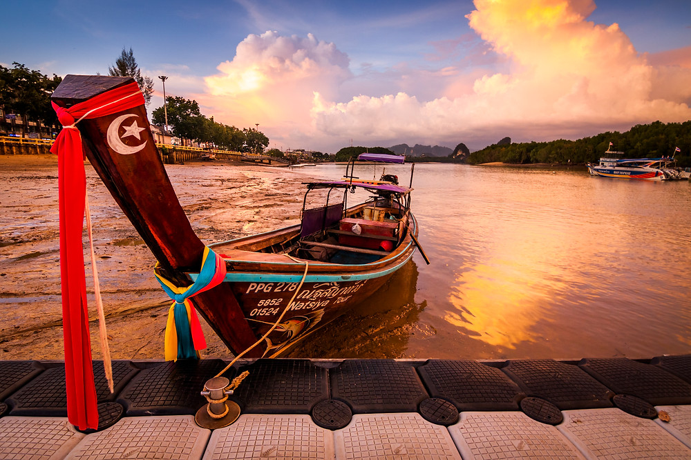 A Long Tail Boat on Krabi River, Thailand at Sunset