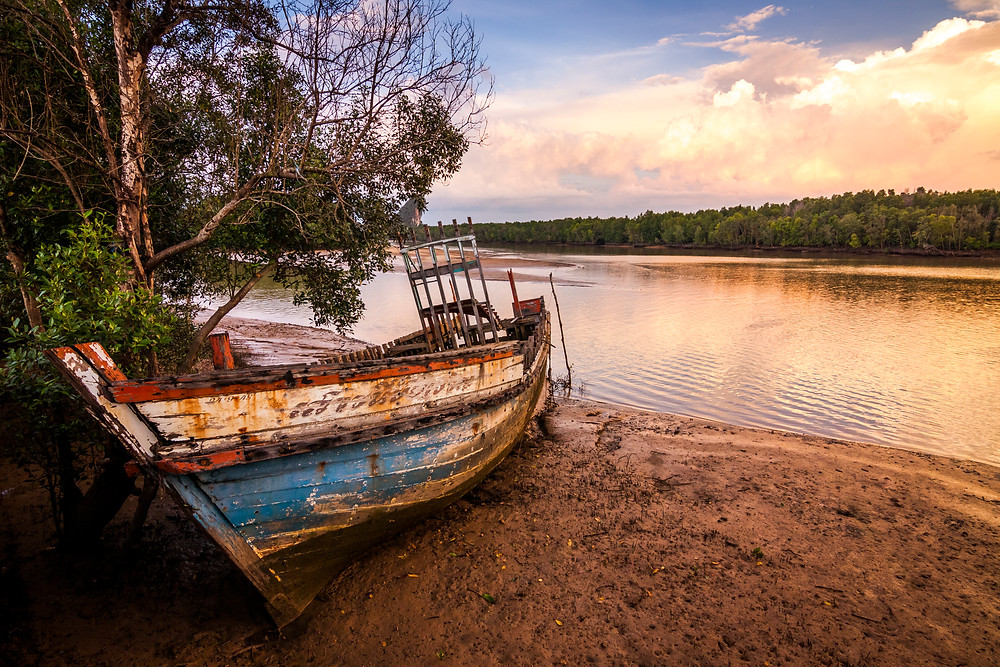 A broken boat on Krabi river, Thailand at Sunset