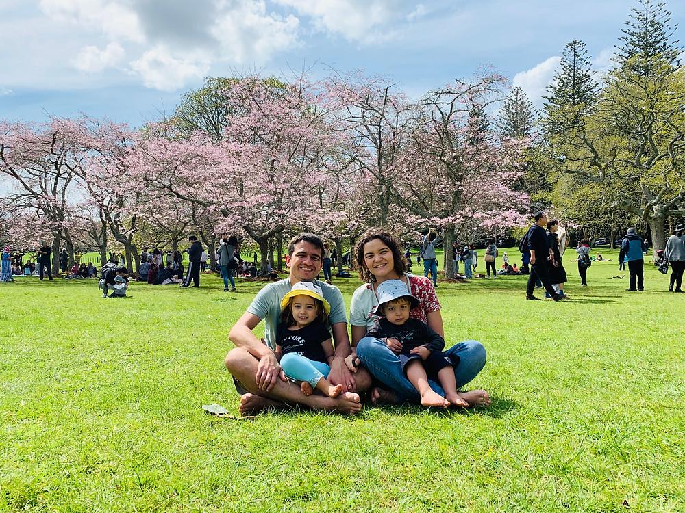 Dani e o marido estão em um gramado, com as crianças no colo, diante de árvores floridas