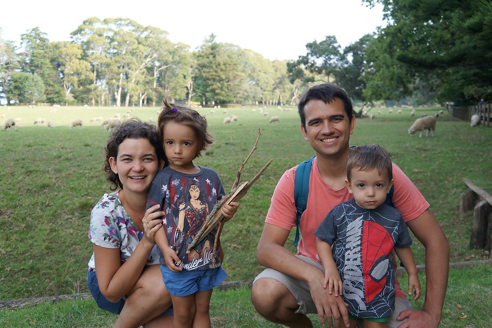 Dani, o marido e as crianças estão em um pasto cheio de ovelhas