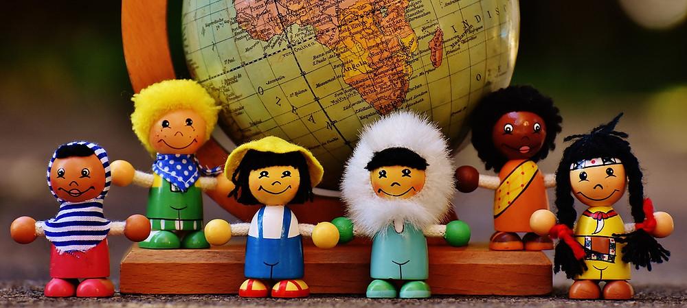 bonequinhos de madeira, de diferentes nacionalidades e culturas (muçulmano, indígena, esquimó, chinês), lado a lado e na frente de um globo terrestre