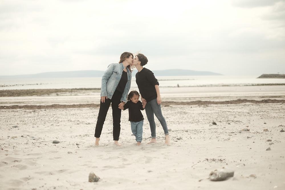 Danny e Mariel se beijam na praia. Mia está entre as duas, de mãos dadas com as duas mães