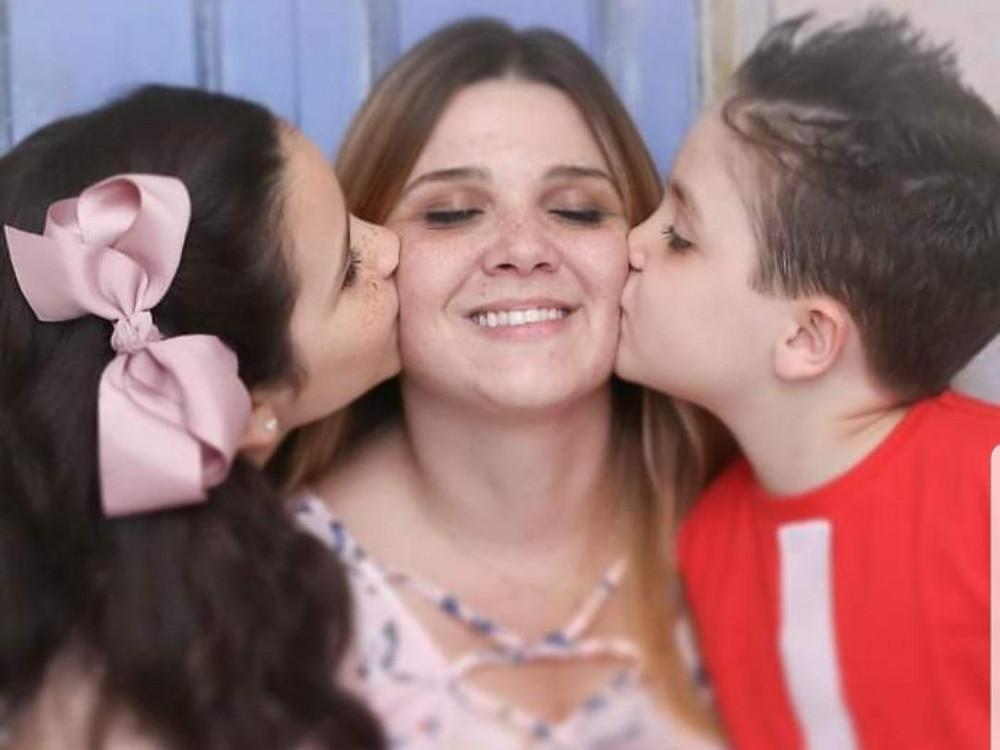 Flávia está ao centro, sorrindo e de olhos fechados. Sophia beija a bochecha direita da mãe enquanto Victor beija a bochecha esquerda. Sophia usa um laço rosa no cabelo e Victor está de camiseta vermelha