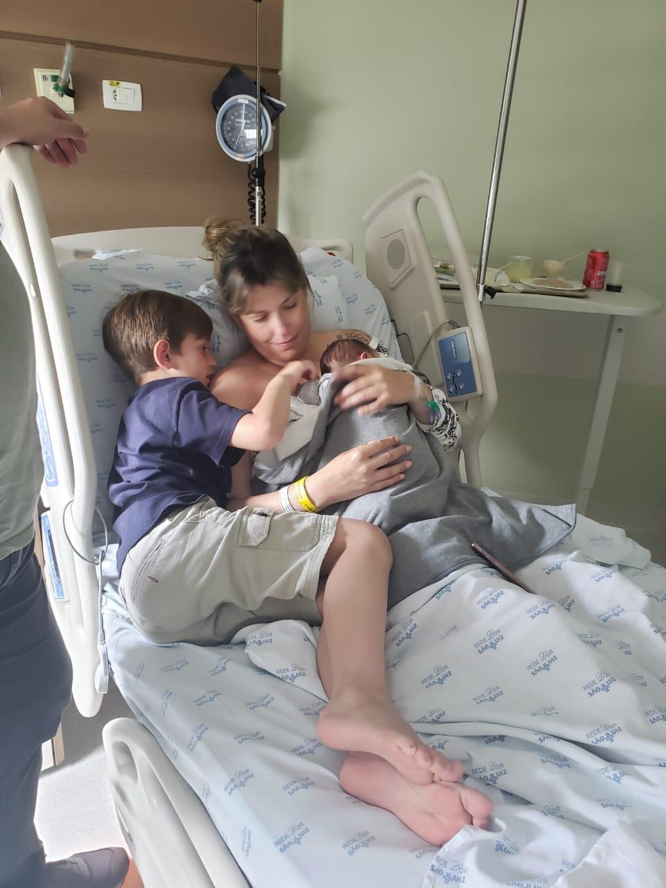 A mãe aparece na cama do hospital com o recém-nascido no colo e o mais velho está deitado ao lado, tentando interagir com o irmão