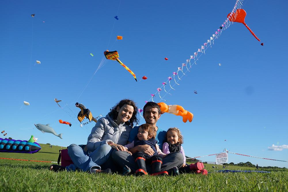 Dani, o marido e as crianças estão sentados num gramado, e o céu atrás deles está cheio de pipas em formatos diferentes, como golfinho e coração