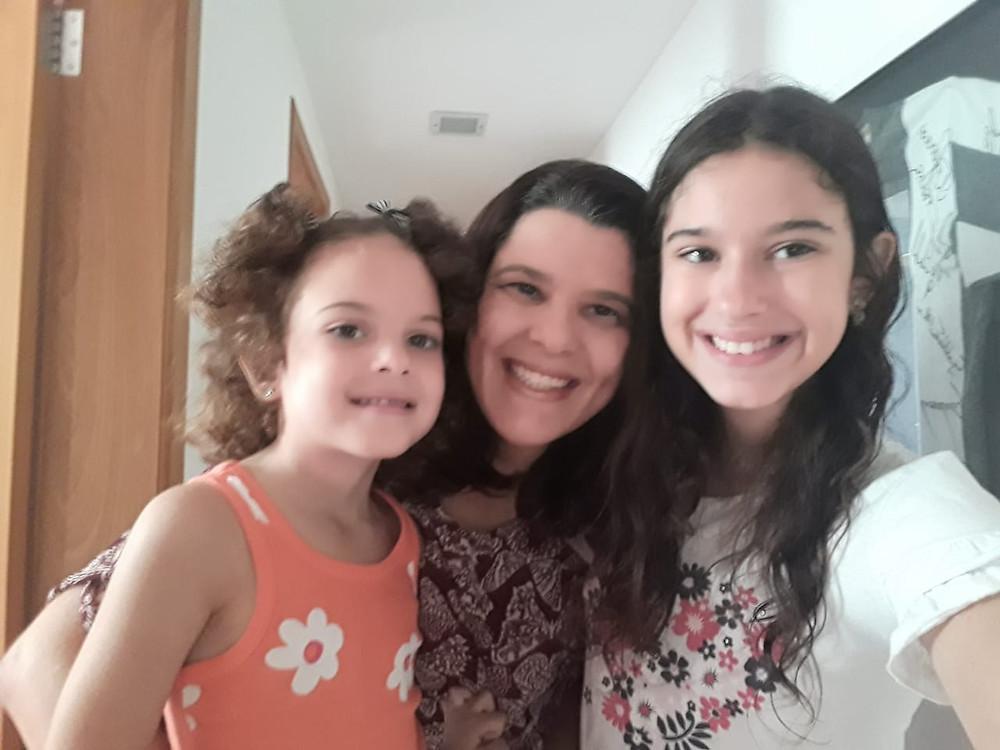 Ana Paula aparece ao centro, sorrindo, abraçando as duas filhas, uma de cada lado