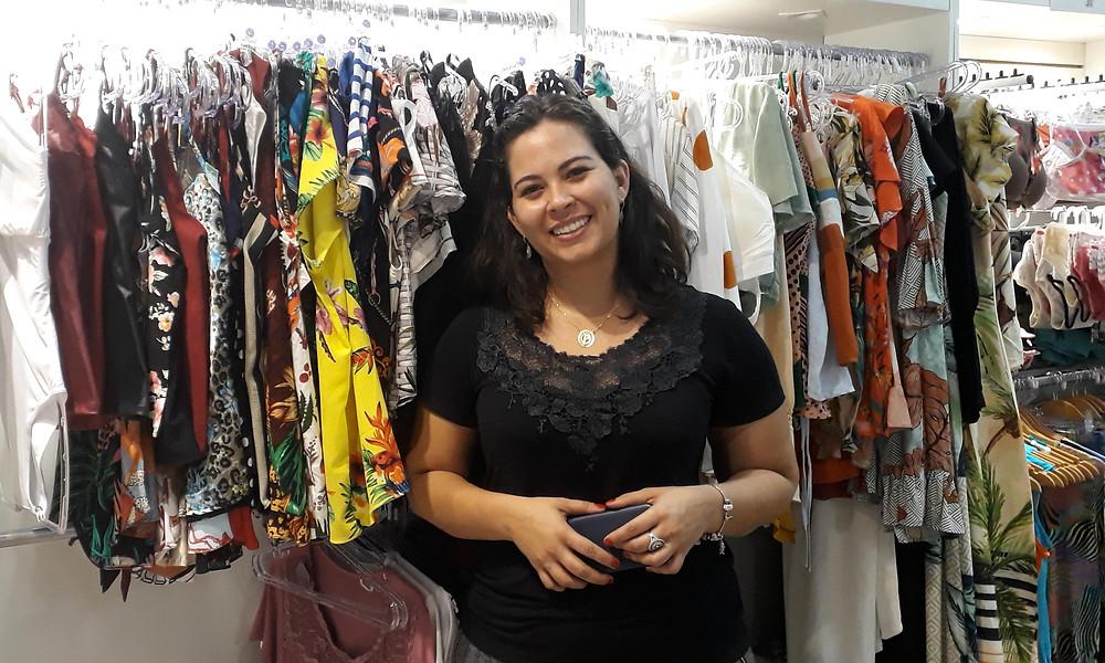Patrícia sorri para a foto diante das roupas de sua marca
