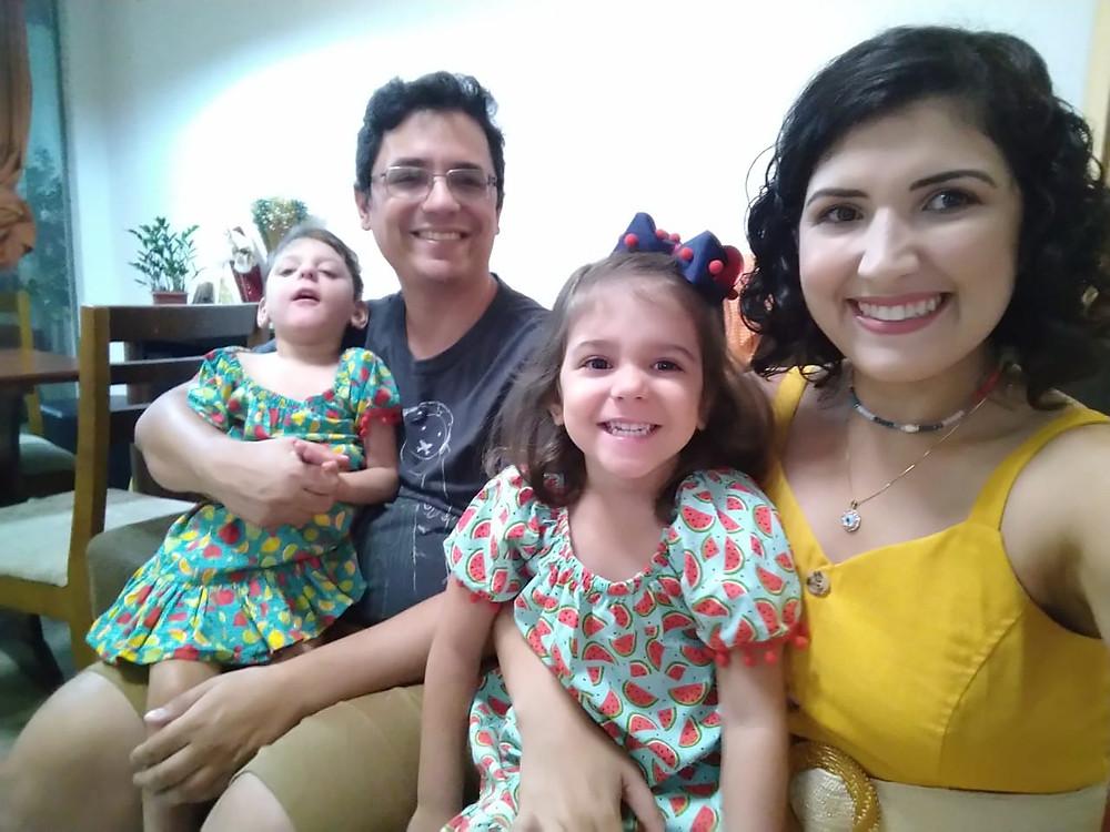 Marcelo e Loren sorriem para a foto, cada um com uma filha no colo