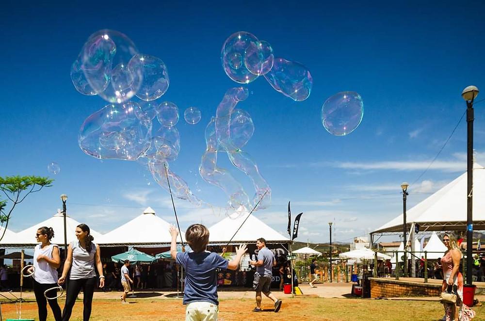 Foto de festa infantil, com garoto de costas brincando com bolhas de sabão gigantes