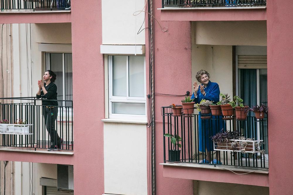 Moça e idosa aplaudem em varandas de prédio