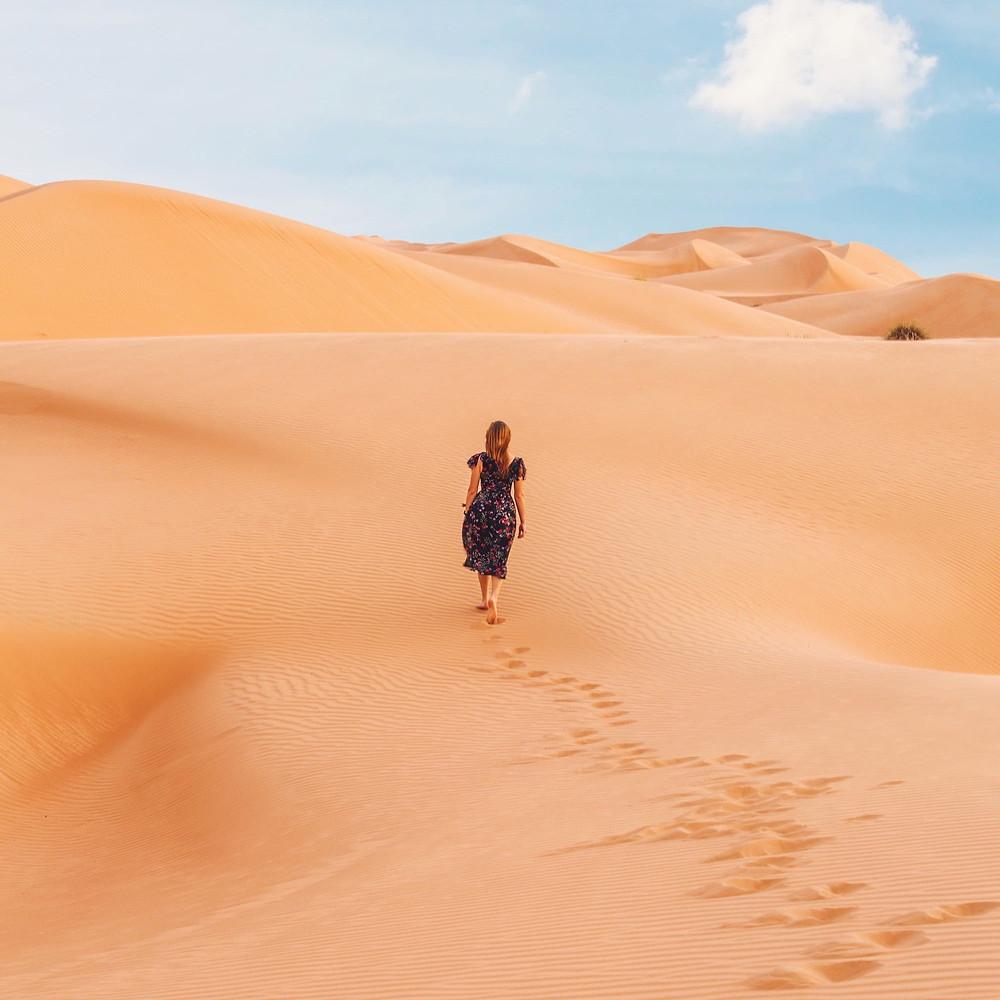 Mulher de vestido roxo vaga pelas dunas de um deserto de areia